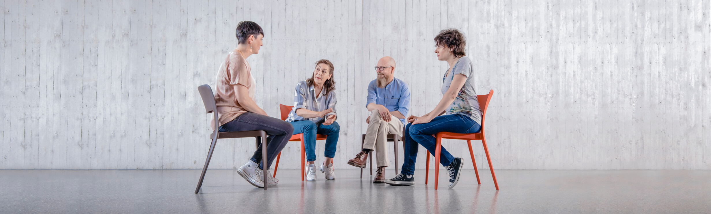 EIne Gruppe sitzt auf Stühlen und unterhält sich