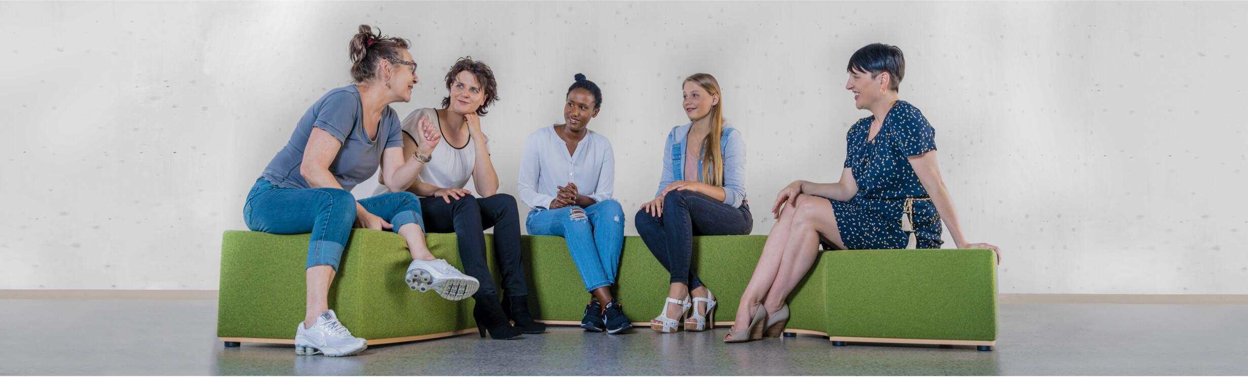Fuenf Frauen sitzen im Halbkreis und unterhalten sich